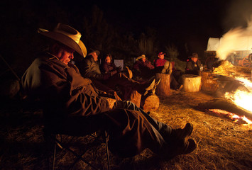 Wrangler Don Pugh sleeps by the fire after gathering approximately 350 horses during Montana Horses' spring drive outside Three Forks