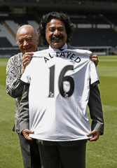 The former owner of Fulham Football Club, Mohamed Al Fayed, and new owner Shahid Khan, pose for photographers at the club's Craven Cottage ground, in west London