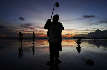 Tourists take pictures during sunset in Kuta beach, Bali resort island