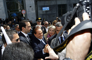 Italian PM Berlusconi shakes the hands of supporters outside Milan's court