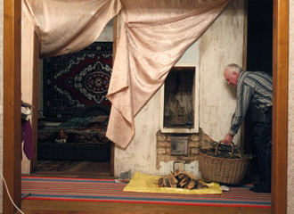 A resident puts firewood into a stove for warmth in his house in the village of Khatsky