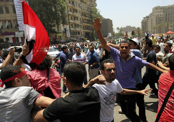 Protesters scuffle and try to attack a supporter of presidential candidate Shafiq during a demonstration at Tahrir Square in Cairo