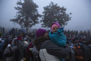Migrants wait to cross the border with Croatia near the village of Berkasovo