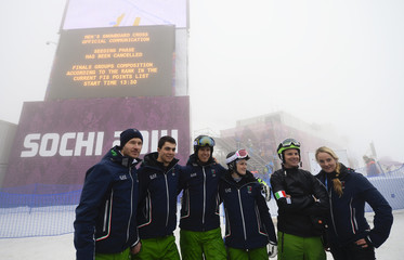 Members of Italian snowboarding team pose for a picture for themselves in front of an information board at the men's snowboard cross event at the 2014 Sochi Winter Olympic Games in Rosa Khutor
