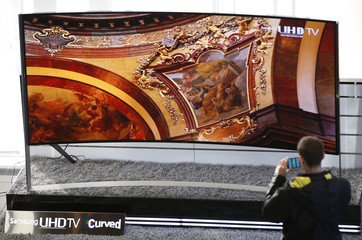A visitor takes photographs of a Samsung Electronics' 105-inch Curved Ultra High Definition TV at the company's headquarters in Seoul