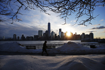New York skyline and the One World Trade Center are seen in the distance as a man makes his commute after a night of snow from New York City to Exchange Place in New Jersey