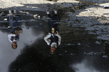 Girls are reflected in oil as they walk near smoke rising from oil wells, set ablaze by Islamic State militants before IS militants fled the oil-producing region of Qayyara