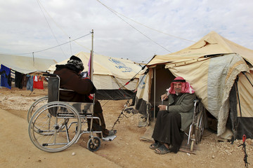 Syrian refugees in wheelchairs are seen in front their tent at Al-Zaatri refugee camp in Mafraq