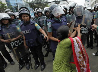 Police officers try to arrest garment worker during protest in Dhaka