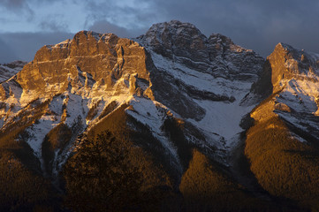 First light of dawn warming up the mountain tops. Canmore, Alberta, Canada
