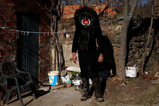 """A man wearing a """"El Diablo"""" (The Devil) mask poses during the """"Los Carochos"""" winter masquerade in Riofrio de Aliste, Spain"""