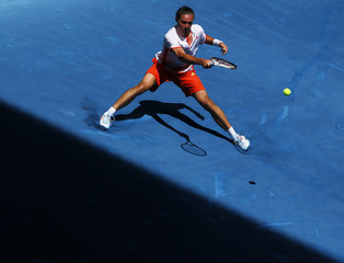 Alexandr Dolgopolov of Ukraine returns the ball to Jo-Wilfried Tsonga of France during their men's singles match at the Madrid Open tennis tournament