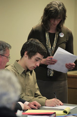 T.J. Lane signs document at juvenile court hearing to determine whether he will be tried as an adult for the shooting death of three students in Chardon, Ohio