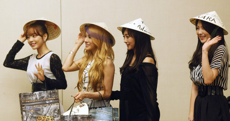 """Members of South Korean girl band Kara wear Vietnamese traditional conical hat """"non"""" after they attended a news conference in Hanoi"""