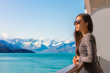 Luxury travel Alaska cruise vacation woman relaxing on balcony enjoying view of mountains and nature landscape. Asian girl sunglasses tourist.