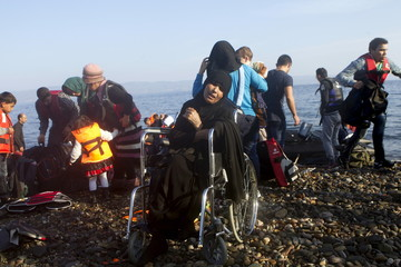 An Iraqi refugee on a wheelchair reacts as refugees and migrants arrive on a dinghy on the Greek island of Lesbos, after crossing a part of the Aegean Sea from the Turkish coast