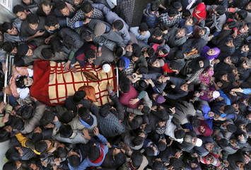 Kashmiri Muslim villagers gather around the body of Dawood Ahmad Sheikh, a suspected militant, during his funeral in Kaimuh