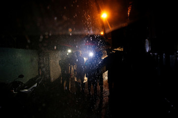 Heavy rain pours as reporters film near the body of a man killed by unidentified gunmen riding motorcycles and left in a narrow alley in Manila