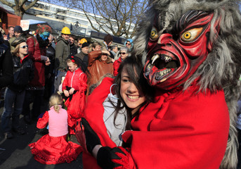 A reveler in a monster costume poses with a fellow reveler during a carnival parade in Berlin,