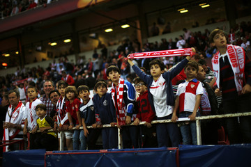 Children look at Sevilla's supporters, known as Biris as they display a banner before the start of the Europa League semi-final first leg soccer match against Valencia at Ramon Sanchez Pizjuan stadium in Seville