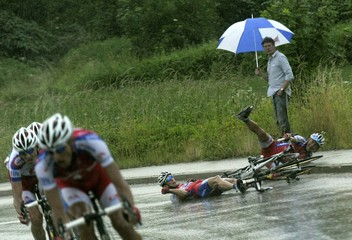 A spectator looks at Jure Zagar and Kristjan Fajt of Adria Mobil, after they fell, during the first leg of the Tour de Slovenia in Medvode