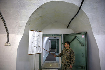 A member of the armed forces of Bosnia and Herzegovina shows a map of Tito's underground secret bunker in Konjic