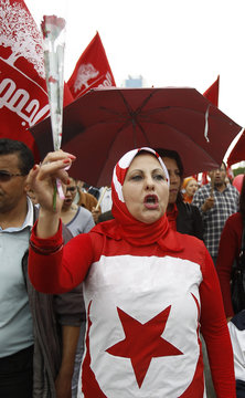 A woman holds a flower and shouts slogans during a May Day march in Tunis