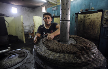 A Palestinian villager collects olive paste to be pressed to extract oil at an old olive press in the West Bank village of Beita near Nablus