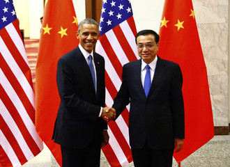 U.S. President Obama shakes hands with China's Premier Li in front of U.S. and Chinese national flags during a meeting at the Great Hall of the People in Beijing