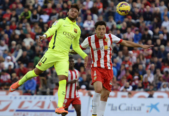 Barcelona's Neymar and Almeria's Ximo Navarro jump for the ball during their Spanish first division soccer match at Los Juegos Mediterraneos stadium in Almeria