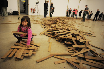 Moira 3 year old daughter of British artist Wilder plays with the wooden slats from her fathers installation 'Untitled # 155' after he kicked it down at the Yorkshire sculpture park near Barnsley