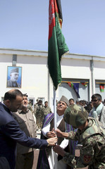 Ashraf Ghani Ahmadzai, Chairman of Afghan Transition Coordination Commission, raises the national flag as Besmillah Muhammadi, Afghanistan's Interior Minister, looks on, during a security transition ceremony in Mazar-e-Sharif