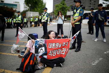 """A supporter of South Korean ousted leader Park Geun-hye cries as she holds a banner that reads """"release President immediately"""" in front of a court in Seoul"""