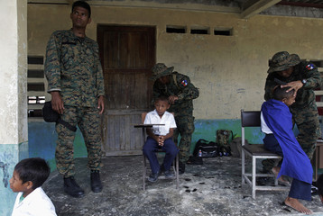 Indigenous Kuna children receive haircuts by Panamanian border police officers on the island of Niadup, in the region of Kuna Yala