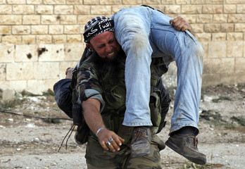 A Free Syrian Army fighter reacts as he carries the body of a fellow fighter after he was killed by a sniper loyal to Syria's President Bashar al-Assad in Khan al-Assal area