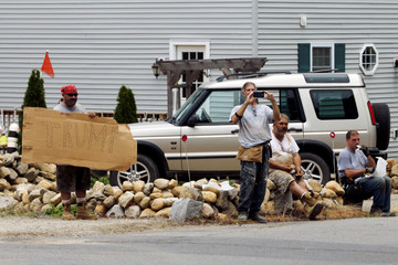 A worker holds a hand-made Trump sign as Obama rides past in his motorcade to a golf outing at Mink Meadows Golf Club during his annual family summer vacation on Martha's Vineyard, in Vineyard Haven, Massachusetts, U.S.