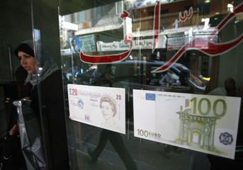 A Palestinian woman walks out of a foreign currency exchange shop in Ramallah