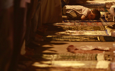 An Egyptian Muslim boy sleeps as his father performs evening prayers during Laylat al-Qadr in the holy month of Ramadan in Alexandria
