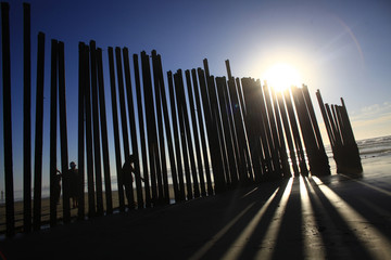 People stand at a wall separating Mexico and the United States in Tijuana as photographed from Imperial Beach