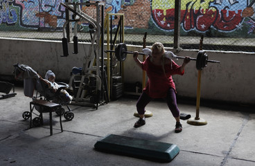 Franco lifts weights next to her 11-month-old son Aquiles at gym under Alcantara Machado viaduct in the Mooca neighborhood of Sao Paulo