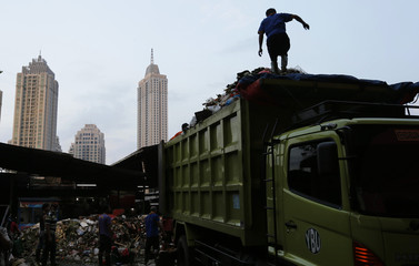 A worker walks on top of a garbage truck at a food market in Jakarta