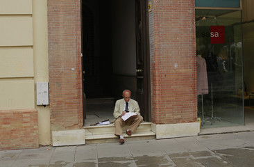 A man sits at a doorway of a building in the Andalusian capital of Seville