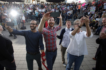 "Plaintiffs Moudi Sbeity and his partner Derek Kitchen, Kody Partridge and her wife Laurie Wood take a a ""selfie"" as they celebrate at a same-sex marriage rally in Salt Lake City, Utah"