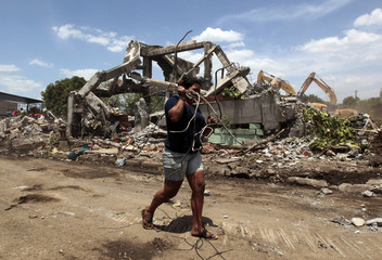 Woman carries scrap iron to sell at the ruins of a building damaged in a 1972 earthquake in the old centre of Managua