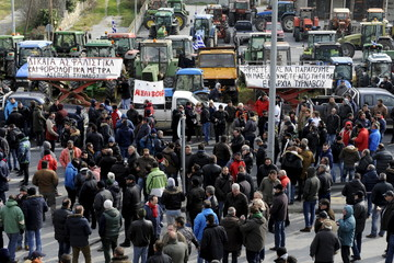 Greek farmers stand next to their parked tractors during a demonstration against planned pension reforms next to the main motorway linking Athens to the north of the country in Tempi, near the city of Larissa