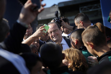 """French President Francois Hollande poses for photos as he visits the """"Red Star"""" soccer club in Saint-Ouen, near Paris"""