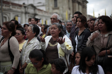 """A woman prays during the """"Jueves de Corpus"""" procession at the Plaza Central in Guatemala City"""