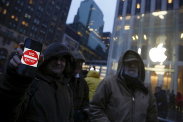A demonstrator holds a sign during a protest against the FBI's request to extract data from iPhones in cases across the country, outside the Apple Store in New York
