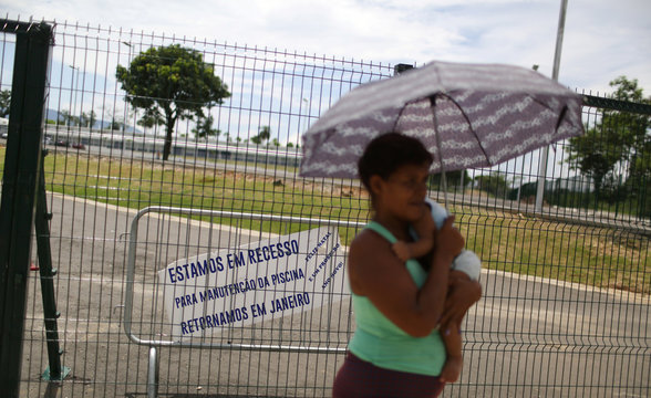 A woman carries a baby in front of the Deodoro Sports Complex, which was used for the Rio 2016 Olympic Games, in Rio de Janeiro