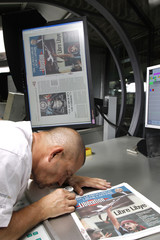 A man inspects the front page of the French daily morning newspaper Liberation at their printing press in La Courneuve